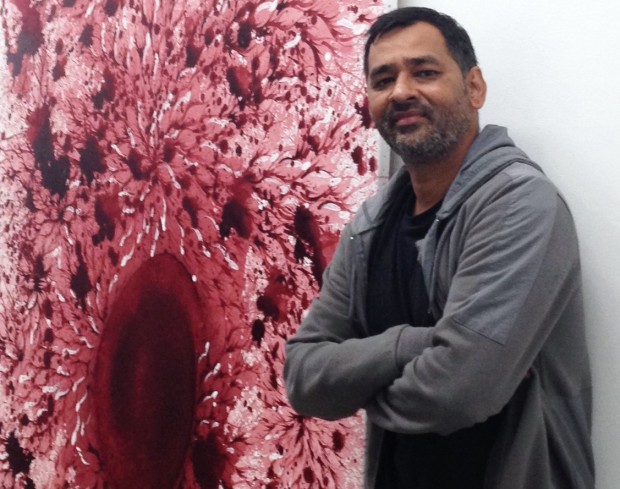 Imran Qureshi standing beside on of his paintings for The Exchange in Penzance